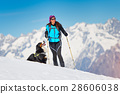 Alpinist girl on skis and sealskins alone with his dog faithful 28606038