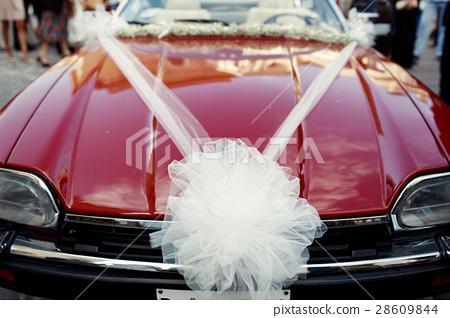 Large bow of veil put on old red Jaguar 28609844