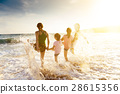 happy young family playing on beach at sunset 28615356