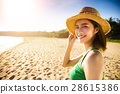young woman walking on the beach at sunset 28615386