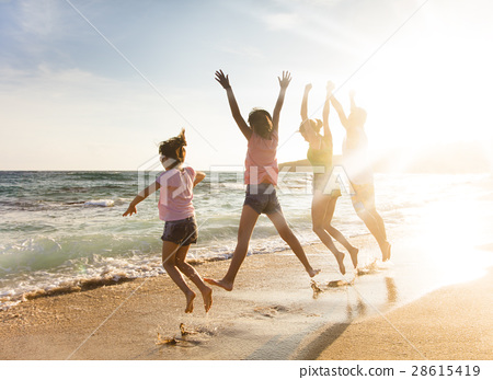 happy young family jumping on beach at sunset 28615419