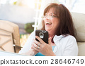 Attractive Middle Aged Woman Laughing While Using Her Smart Phon 28646749