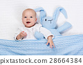 Baby boy playing with bunny toy in bed 28664384
