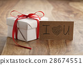 white paper gift box with thin red ribbon bow on 28674551