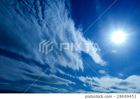 the Sun and white fluffy clouds on a blue sky 28699451