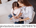 Professional doctor giving little girl a piece of 28708978