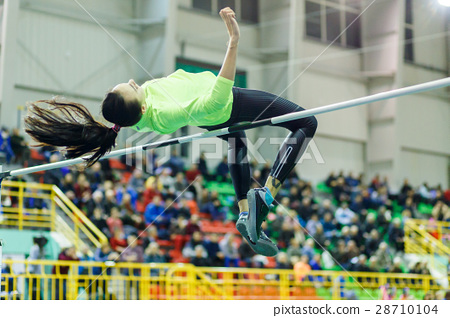 Young girl jumping over bar in high jump contest. 28710104
