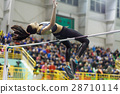 Young girl jumping over bar in high jump contest. 28710114