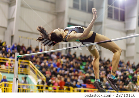 Young girl jumping over bar in high jump contest. 28710116
