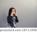 Little asian child play the harmonica 28711998