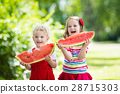 Kids eating watermelon in the garden 28715303