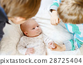 Two little kids boys playing with newborn baby 28725404