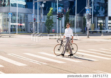 young man with bicycle on crosswalk in city 28751772