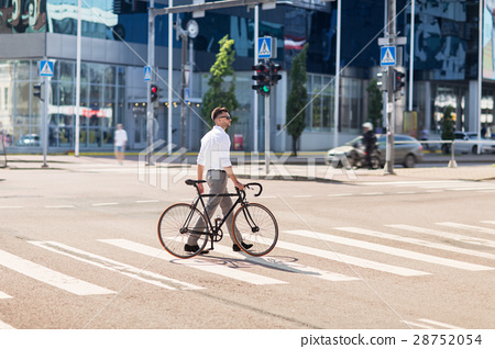 young man with bicycle on crosswalk in city 28752054