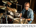 male musician playing drums and cymbals at concert 28753924