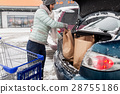 woman loading food from shopping cart to car trunk 28755186