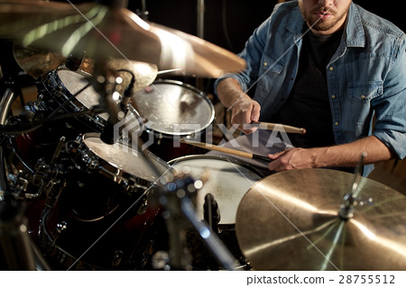 male musician playing drums and cymbals at concert 28755512