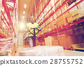 man carrying loader with goods at warehouse 28755752