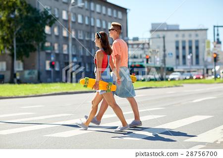 teenage couple with skateboards on city crosswalk 28756700