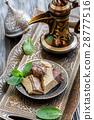 Bronze tray with tahini halva and pitcher. 28777516