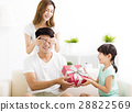 Father receiving gift box from wife and daughter 28822569
