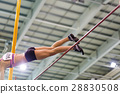 Young athletic woman vaoulting over bar with pole 28830508