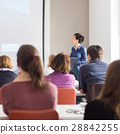 Woman giving presentation in lecture hall at 28842255