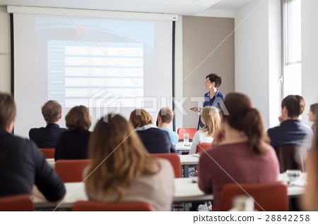Woman giving presentation in lecture hall at 28842258