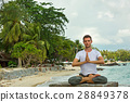 Man does yoga on the beach 28849378