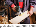 Carpenter at work with the sander 28863280