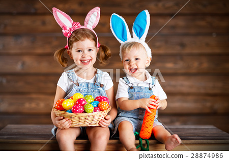 Happy kids boy and girl dressed as Easter bunnies with basket of 28874986