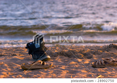sneakers with sea wave on sand background 28902750