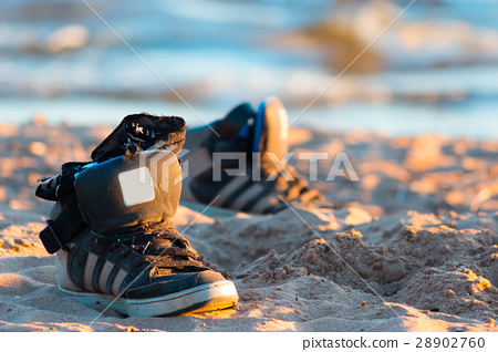 sneakers with sea wave on sand background 28902760