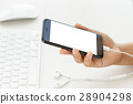 hand holding phone  showing white screen on desk 28904298