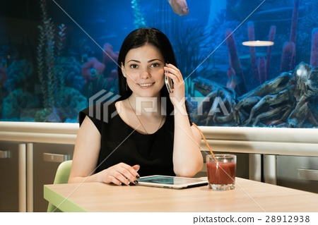 Brunette woman talking on a cellphone indoors 28912938