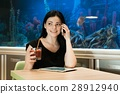 Brunette woman talking on a cellphone indoors 28912940