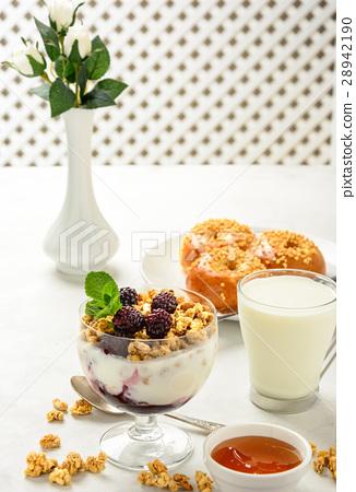 Breakfast of granola, buns brioche and milk. 28942190