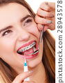 Woman smiling cleaning teeth with braces 28943578