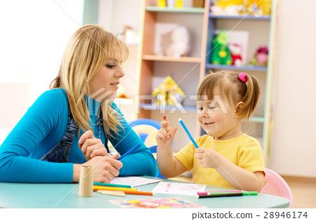 Teacher with child in preschool 28946174
