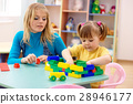 Teacher and preschooler play with building bricks 28946177