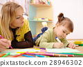 Teacher with child in preschool 28946302