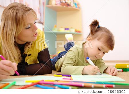 Teacher with child in preschool 28946302