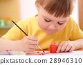 Child draws with paints in preschool 28946310