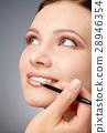 Applying lip gloss for young girl 28946354
