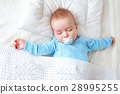 baby sleeping on blue blanket 28995255
