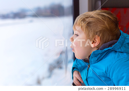 Cute little toddler boy looking out train window 28996911