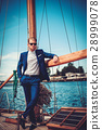 Stylish wealthy man on a luxury wooden regatta 28999078