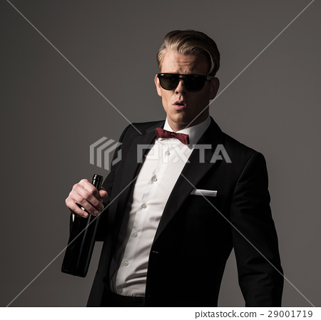 Sharp dressed man in black suit with bottle of 29001719