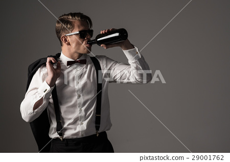 Sharp dressed man in black suit with bottle of 29001762