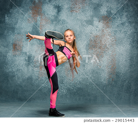 Young girl break dancing on wall background. 29015443